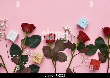 True love. Show her your feelings with red roses, cute gift boxes and tender wild flowers. Pink background - Stock Photo