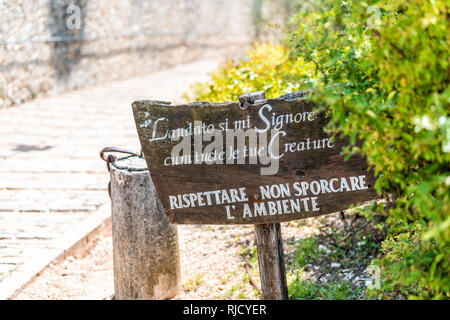 Assisi, Italy - August 29, 2018: Town or village city in Umbria with San Damiano church sign for silence respect during sunny summer day and road path - Stock Photo