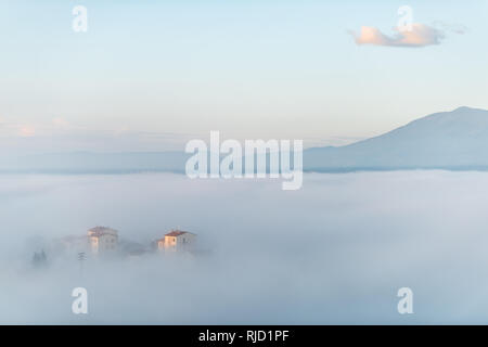 Chiusi Scalo mist fog sunrise of rooftop houses buildings in Umbria, Italy near Tuscany with soft clouds covering blanketing town cityscape skyline in - Stock Photo