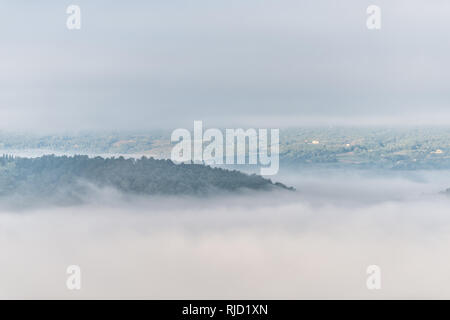 Chiusi Scalo mountain mist fog sunrise and villas houses in Umbria and Tuscany in Italy with soft clouds covering blanketing inversion in summer - Stock Photo