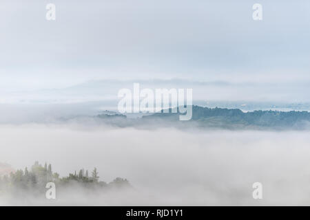 Chiusi Scalo mountain mist fog sunrise and houses in Umbria and Tuscany in Italy with soft clouds covering blanketing inversion in summer - Stock Photo