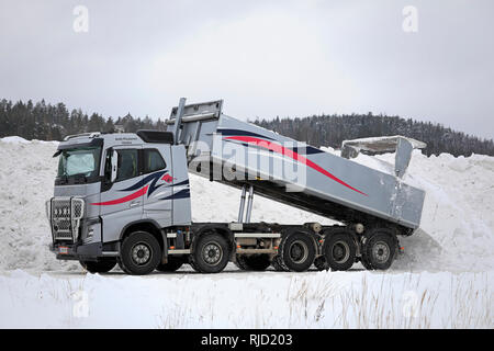 Salo, Finland - February 2, 2019: Volvo FH16 750 tipper truck unloads snow cleared from streets and parking lots at municipal snow dumping area. - Stock Photo
