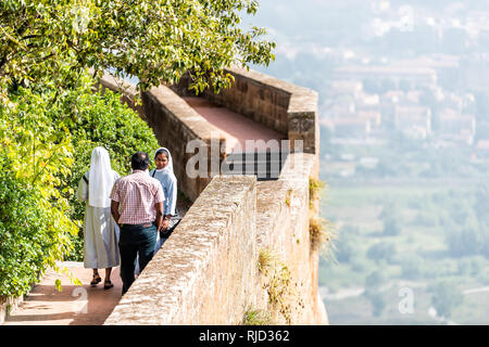 Orvieto, Italy - September 3, 2018: Small historic medieval town village in Umbria with city walls fortress fort tower and nuns tourists on cliff with - Stock Photo
