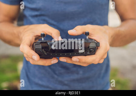 Man holds remote controller with his hands and controls the drone. New technologies and innovations concept. - Stock Photo
