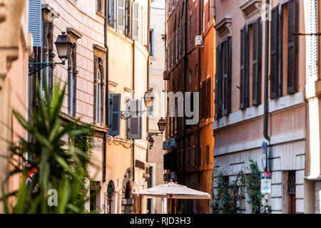 Rome, Italy - September 4, 2018: Italian outside traditional narrow empty alley with nobody on street in historic city summer plants lanterns - Stock Photo