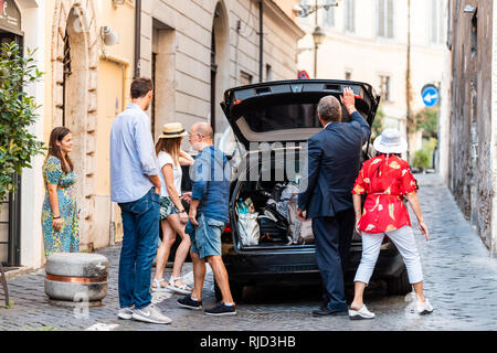 Rome, Italy - September 4, 2018: Narrow city town Via street by hotel with people departing by taxi on narrow road and family with driver - Stock Photo