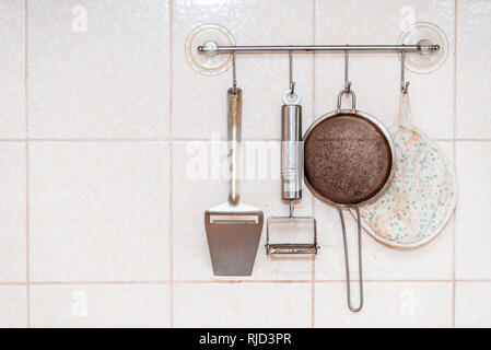 Kitchen utensils hanging on wall with sieve, metal peeler and towel mounted with suction cups closeup of tiled wall - Stock Photo
