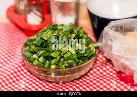 Closeup of chopped green onions scallions in glass bowl homegrown garden produce with red checkered tablecloth Ukraine or Russia dacha country rustic  - Stock Photo