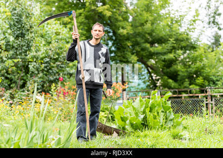 Back of young man farmer in garden standing with sickle scythe rake tool in green summer in Ukraine by well faucet - Stock Photo