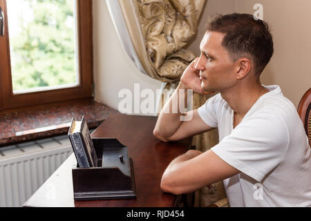 Young man sitting on chair by rustic vintage wooden antique table and window blinds in boutique hotel or home office - Stock Photo