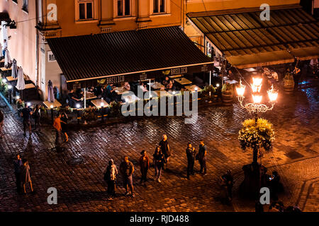 Lviv, Ukraine - July 31, 2018: Aerial high angle Basilico restaurant Ukrainian city in old town market square with illuminated night people walking da - Stock Photo