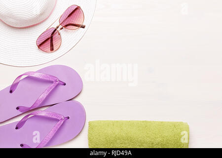 Beach accessories on a white background - glasses, towel, slippers and hat. summer comes concept - Stock Photo