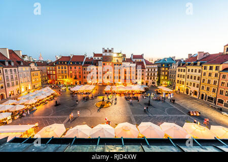 Warsaw, Poland - August 22, 2018: Cityscape with high angle view of architecture rooftop buildings and dark sky in old town market square at night wit - Stock Photo