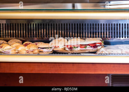 Display of many large sandwiches behind glass window of store stuffed with ham cheese and tomatoes in Italy with croissants and buns - Stock Photo