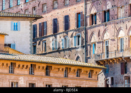 Siena, Italy Street in historic medieval old town village in Tuscany with facade exterior architecture on square during sunny summer day - Stock Photo