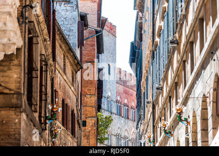 Siena, Italy Street in historic medieval old town village narrow alley in Tuscany with facade exterior architecture during sunny summer day - Stock Photo