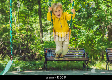 A boy in a yellow sweatshirt sits on a swing on a playground in autumn. - Stock Photo