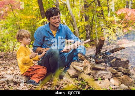 Happy father doing barbecue with his son on an autumn day. - Stock Photo