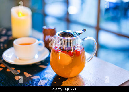 Delicious tea with ginger, apple and and rosehip in a transparent teapot. Cup and candle in the background out of focus - Stock Photo