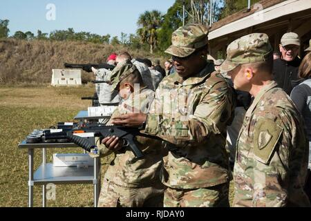 U.S. Army MAJ Kendall Robinson, Division Chief, Capabilities and Requirements, Joint Non-Lethal Weapons Directorate shows a Soldier an FN303 compressed air launcher. Joint service military personnel from U.S. Central Command (USCENTCOM) and supporting commands had the opportunity to fire non-lethal weapons (NLW) at the MacDill Air Force Base firing range during a familiarization event (FAMFIRE), Jan. 18, 2018. The FAMFIRE was a demonstration of NLW capabilities, and a show of how NLW may be used in conjunction with lethal weapon systems to enhance effectiveness and efficiency in military opera - Stock Photo