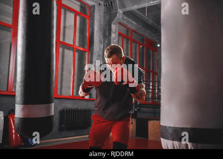 Handsome muscular sportsman in sports clothing boxing on heavy punch bag. Hard training on boxing gym background - Stock Photo