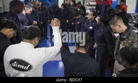 ATLANTIC OCEAN (Jan. 21, 2018) -- Sailors assigned to USS Gerald R. Ford (CVN 78) gather in prayer following the ship's first gospel service held in the forecastle. Ford is underway conducting test and evaluation operations. - Stock Photo
