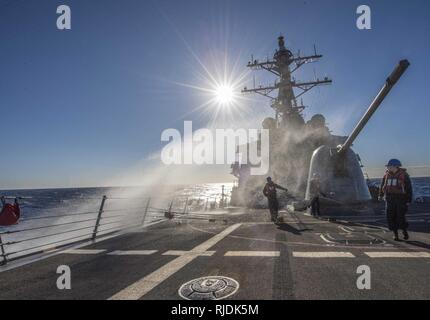 MEDITERRANEAN SEA (Jan. 22, 2018) A wave crashes over the forecastle of the Arleigh Burke-class guided-missile destroyer USS Carney (DDG 64) while underway in the Mediterranean Sea. Carney is forward-deployed to Rota, Spain, on its fourth patrol in the U.S. 6th Fleet area of operations in support of regional allies and partners, and U.S. national security interests in Europe. - Stock Photo