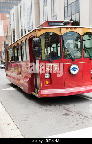 A trolley drives through historic downtown Asheville, North Carolina, USA. - Stock Photo