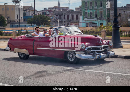 A typical old american car taxi full of tourists drives along the Malecon Embankment near the Old Town in Havana, Cuba - Stock Photo