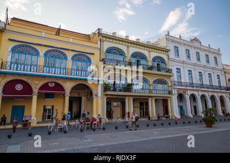Wall to wall spanish colonial-style buildings with people sitting outside of a cafe at the Old Town Square Plaza Vieja in Havana Cuba - Stock Photo