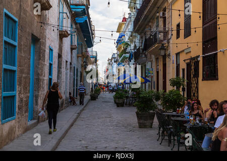 Scene on a typical narrow street in the Old Town in Havana in Cuba. Local people  walking along and tourists and Cubans dining outside of a restaurant - Stock Photo