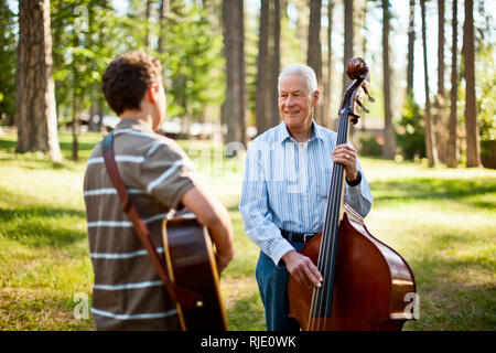 Smiling senior man playing a double bass while his grandson plays an acoustic guitar in a forest. - Stock Photo