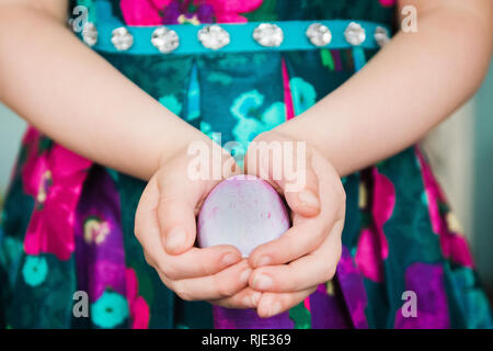 young school girl in easter dress holding dyed easter egg - Stock Photo