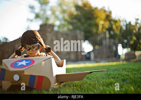 Young boy having fun pretending to be a pilot in a cardboard plane. - Stock Photo