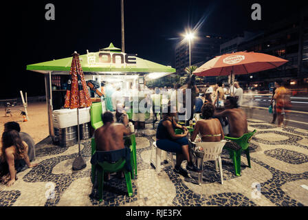 RIO DE JANEIRO-FEB.10 ,2009: night out in ipanema part of rio, people sit in a bar in the walkway near the beach drinking and enjoying music - Stock Photo