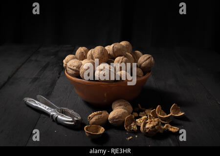 Walnuts in a bowl on dark background. Low-key image of nuts on black rustic table, artistic light and shadow technique - Stock Photo