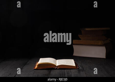 Open book of Bible on dark table. Low-key image of New Testament in bright light among darkness and shadows - Stock Photo