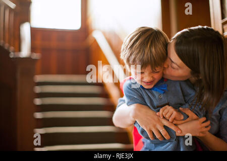 Mother kissing her young son on the cheek. - Stock Photo