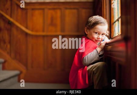 Young boy wearing a superhero cape. - Stock Photo