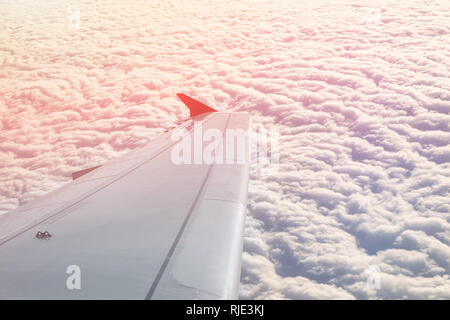 Plane flying over clouds at dawn. Airplane wing over beautiful cloudscape during dramatic colorful sunset or sunrise. Travel and vacation concept - Stock Photo