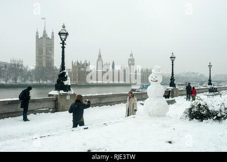 A snowy day on the South Bank with a large snow man, a people walking and in the background the Houses of Parliament visible through falling snow. - Stock Photo