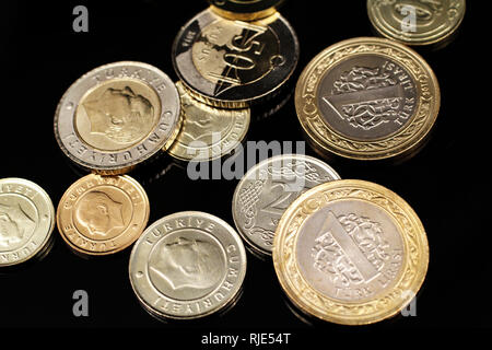 A macro image of an assortment of Turkish coins on a reflective black background - Stock Photo