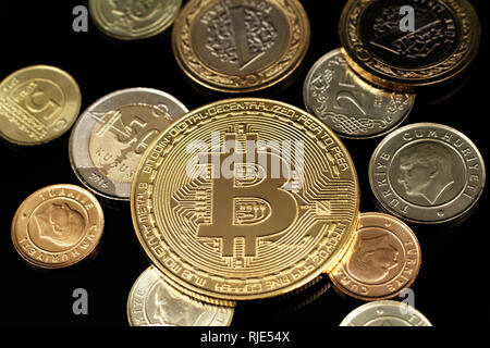 A macro image of an assortment of Turkish coins and a golden bitcoin on a reflective black background - Stock Photo