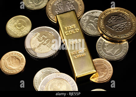 A macro image of an assortment of Turkish coins and a gold one ounce ingot on a reflective black background - Stock Photo