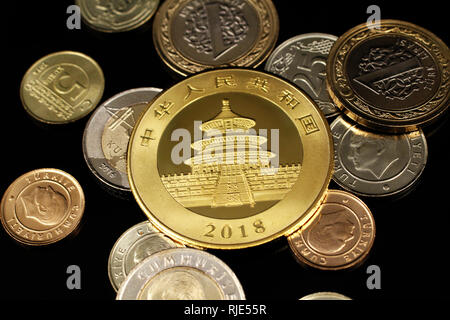 A macro image of an assortment of Turkish coins and a gold Chinese one ounce coin on a reflective black background - Stock Photo