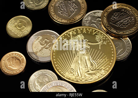 A macro image of an assortment of Turkish coins and a gold American one ounce coin on a reflective black background - Stock Photo