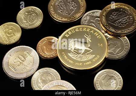 A macro image of an assortment of Turkish coins and a gold South African one ounce coin on a reflective black background - Stock Photo