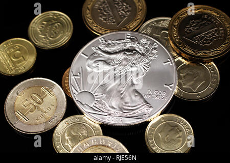 A macro image of an assortment of Turkish coins and a silver American one ounce coin on a reflective black background - Stock Photo