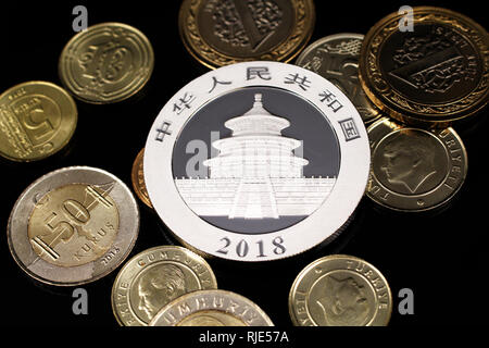 A macro image of an assortment of Turkish coins and a silver Chinese one ounce coin on a reflective black background - Stock Photo