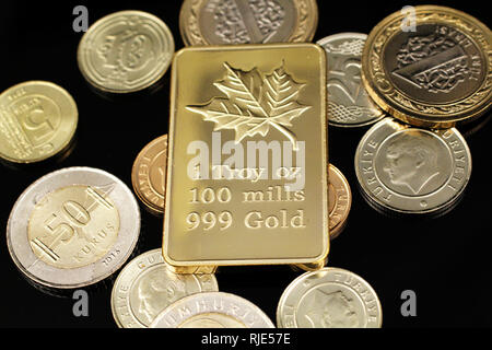 A macro image of an assortment of Turkish coins and a gold Canadian one ounce ingot on a reflective black background - Stock Photo